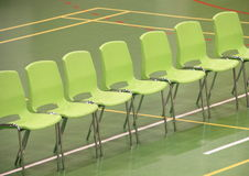 Line of green chairs in sports hall Stock Images