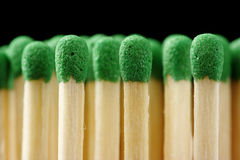 Line of green matchsticks on black background Royalty Free Stock Photography
