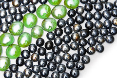 Line of green stones among black stones Stock Photo