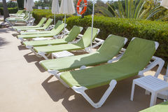 Line of green sunloungers on swiming pool Stock Photography