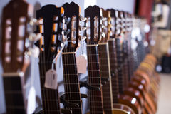 Line of heads of acoustic guitars Stock Image