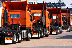 Line of heavy haulage orange trucks. Convoy of heavy haulage bright orange truck cabs Royalty Free Stock Images