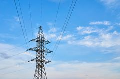 A line of high-voltage cables against a blue sky with clouds. stock photography