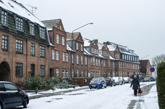 Line of  houses with a backyard and a lot of snow on the roof and cars and roadthe background Royalty Free Stock Photo