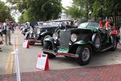 A line of incredible cars down the street. Geneva Concours D'Elegance had too many cars to feature just one. Here is one row of cars that goes as far as the eye Stock Images