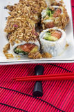 Line of japanese rolls on the white plate with red chopsticks Stock Photos