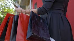 On-line-Käufe, Käufermädchen benutzt Handy für das Kaufen und das Zahlen im Internet am Saisonverkauf, viele Einkaufstaschen stock footage