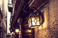 Line of lanterns in Venice at night on the vintage wall Royalty Free Stock Photos