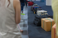 Line of luggage and belonging and people waiting for claim on ar Royalty Free Stock Photo