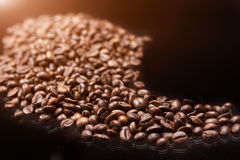 Line made of Roasted Coffee Beans Over Black Background. Light E Stock Image