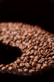 Line made of Roasted Coffee Beans Over Black Background. Stock Image