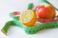 Line measure with lemon and red apple Stock Photography