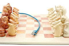 On line meets offline gaming. Blue ethernet cable running between chess set to depict o nline gaming Stock Photos