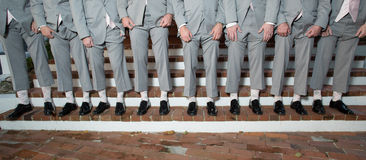 Line of men's legs and shoes. Line of men wearing gray suits or tuxedos and black shoes stock image