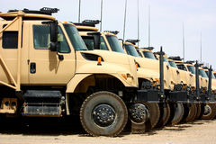 Line of military transportation trucks. Line of desert military transportation trucks parked outdoor Royalty Free Stock Images