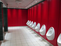 Urinals in a public toilets. A line of modern urinals in a public toilet with a red wall in the background Stock Photography
