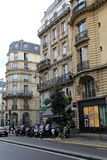 Line of motorcycles on sidewalk of busy street,downtown Paris,France,2016 Royalty Free Stock Photo