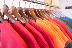 Line of multi colored clothes on wooden hangers in store. Sale Royalty Free Stock Photography