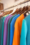 Line of multi colored clothes on wooden hangers in store. Sale Stock Images