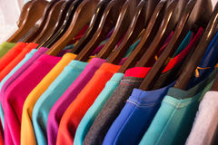 Line of multi colored clothes on wooden hangers in store. Sale Stock Photo
