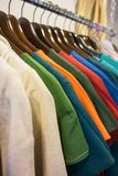 Line of multi colored clothes on wooden hangers in store. Sale Stock Image