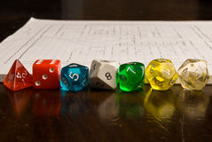 Role Play style dice and map. A line of multi-colored role play dice sitting in front of a game map, drawn on graph paper. A shallow depth of field used to throw Stock Photos