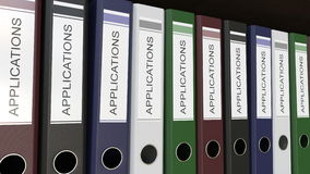 Line of multicolor office binders with Applications tags 3D rendering Royalty Free Stock Image