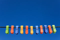 Line of multicolor plastic clothes pegs. Hanging in front blue sky Royalty Free Stock Images