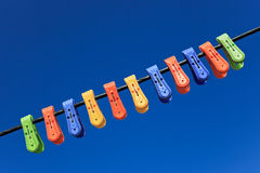 Line of multicolor plastic clothes pegs Stock Photography