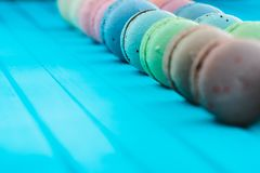 Line of multicolored macaron or macaroons on a turquoise wooden background, almond cookies in pastel tones on a blue. Table, selective focus Stock Photo