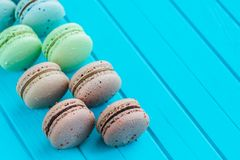 Line of multicolored macaron or macaroons on a turquoise wooden background, almond cookies in pastel tones. Top view. Selective focus Stock Photography