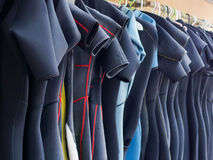 Line of Multiple Hanging Wetsuits royalty free stock photography