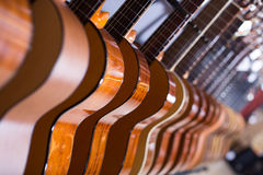Line of new acoustic guitars Stock Photos
