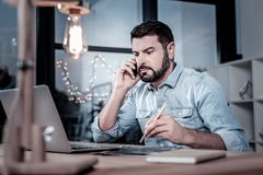 Occupied reliable employee having phone conversation and using his laptop. royalty free stock photos