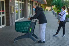 Line Of Italian People During Coronavirus Pandemic: Social Distancing Of A Couple Queuing Up With A Shopping Cart For Groceries Royalty Free Stock Photos