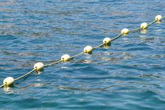 Line Of Yellow Buoys Against The Blue Sea. Restriction On Open Water. Glare And Ripples On The Water Stock Photography