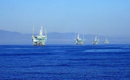 Line of Oil Rigs off California Coast Shot from Ocean. Diagonal Row of Oil Rigs or Derricks Sitting in the Ocean off the California Coast Shot from a Boat Stock Photos