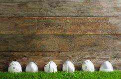 Line of painted Easter eggs on green lawn against wooden background. Space for text royalty free stock photos