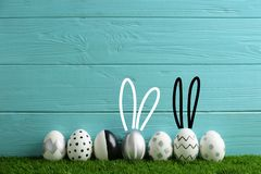 Line of painted Easter eggs on green lawn against wooden background. Space for text stock image