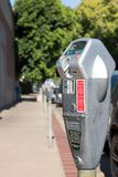 Line of parking meters in city. A line of parking meters; focused on one with others blurred in background Stock Photos