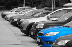 Line from the passenger cars. Black-and-white cars are on the parking and only one blue colored automobile Royalty Free Stock Photo
