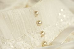 Line of pearl buttons on a wedding dress. Closeup of pearl buttons on an ivory wedding dress with white ribbons Royalty Free Stock Photography