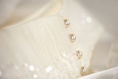 Line of pearl buttons on a white wedding dress. Closeup of pearl buttons on a white wedding dress with white ribbons Royalty Free Stock Photos