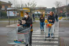 A line of people with face masks standing in line with shopping carts to stock up groceries. Italians prepare for lockdown