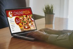 Man ordering pizza by internet with a laptop computer. Stock Photography