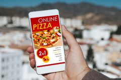 On line pizza shopping app in a mobile phone screen. Hand holding device. Stock Photos