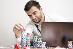 On-line-Poker, der Chips beim Lächeln stapelt Stockbilder