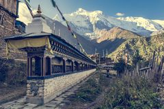 Line of praying wheels at village entrance in Nepal. Royalty Free Stock Images