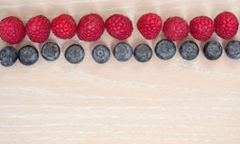 Line of rasberry and bilberry on the wooden background. Twin line of raspberry and bilberry on the wooden background Royalty Free Stock Image