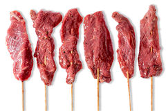 Line of raw beef kebabs on sticks Royalty Free Stock Images